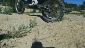 Cruz do motociclista o poço As rodas do enduro passam o poço pequeno Feche acima do movimento lento vídeos de arquivo