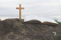 A cruz e a Bíblia estão na rocha, nos pecados e na oração fotos de stock