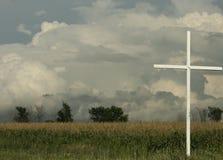 Cruz en campo con las nubes de tormenta arriba Imagenes de archivo