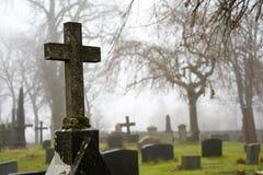 Cruz en el cementerio brumoso 2 del otoño Imagenes de archivo