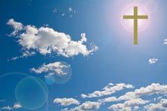Cruz en el cielo con la flama del sol detrás de ella foto de archivo libre de regalías