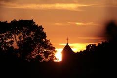 Cruz en el cielo rojo Foto de archivo libre de regalías