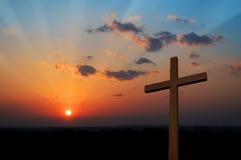 Cruz en la puesta del sol Imágenes de archivo libres de regalías
