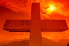 Cruz en la puesta del sol Foto de archivo libre de regalías