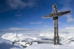 Cruz en una cumbre de la montaña imagenes de archivo