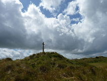 Cruz en una ladera con las nubes Fotos de archivo