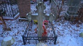 Cruz grave antigua con las flores artificiales almacen de metraje de vídeo
