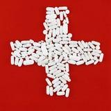 Cruz hecha de las píldoras blancas (fondo rojo) Foto de archivo