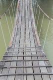 A cruz longa de madeira velha da ponte de corda do pendente o córrego, em nat Fotografia de Stock