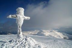 Cruz na cimeira do inverno imagem de stock
