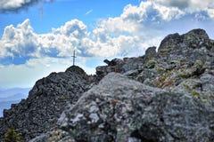 Cruz na parte superior rochosa da montanha Fotografia de Stock Royalty Free