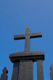 Cruz negra en fondo del cielo azul Imagen de archivo