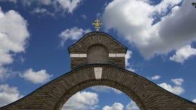 Cruz ortodoxo contra o céu com nuvens filme