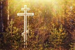 Cruz ortodoxo da adoração na floresta no lado da estrada na entrada da vila no outono foto de stock