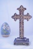 Cruz púrpura adornada con el huevo del lirio de pascua imagen de archivo