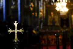 Cruz redondeada de oro metálica dentro de una iglesia imagenes de archivo