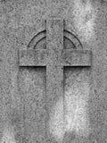 Cruz religiosa grabada en relieve en un tombston antiguo resistido del granito foto de archivo
