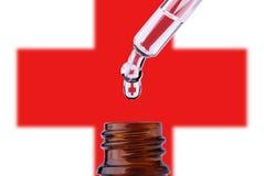 Cruz Roja con gota en la pipeta sobre la botella Fotos de archivo