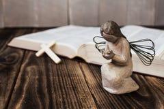 Cruz y biblia del ángel en fondo de madera foto de archivo