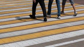 Cruzamento pedestre na estrada de pedra Listras brancas e amarelas em que três homens passam nas sapatilhas Pés dos povos nas cal imagem de stock royalty free
