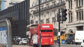 Cruzamento quadrado do ônibus do ônibus de dois andares do circo de Piccadilly antes de anunciar o painel filme
