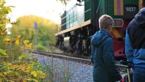 Cruzamento Railway A família está perto da estrada de ferro e olha a locomotiva de passagem Autumn Park, um pitoresco filme