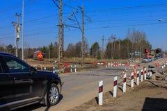 Cruzamento railway fechado passeios do trem, carros que esperam a abertura da barreira piscando um sem?foro imagens de stock