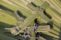 Cruzes da palma e grânulos do rosário em folhas de palmeira Fotografia de Stock Royalty Free