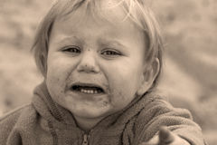 Cry baby. Portrait of a cute little caucasian baby boy with unhappy facial expression crying Royalty Free Stock Photography