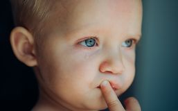 He is a cry baby. Little baby crying. Baby with tear rolling down his cheek. Little boy child with sad face. Sadness.  royalty free stock image
