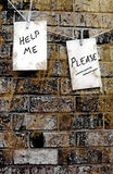 Cry For Help. Help me please written on grungy paper on brick wall Royalty Free Stock Photo