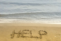 A Cry for Help. The word help is carved in the sand in the conceptual photo Royalty Free Stock Photos