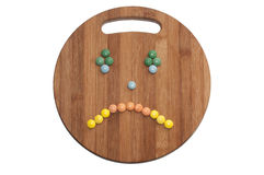 Cry smiley of the round chocolate candies on a wooden board Stock Images