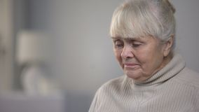 Crying aged woman taking pills, suffering from incurable disease, hospital. Stock footage stock video footage