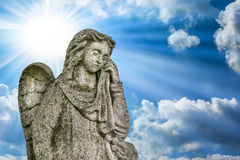 Crying angel. Sunlight and clouds background. Stock Photo
