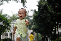 Crying asian baby. It is a cute chinese baby, he is crying and running in the outdoor Stock Photos