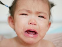 Crying Asian baby girl, one year old, with tears. Selective focus and close up shot Stock Photo