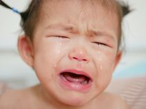 Crying Asian baby girl, one year old, with tears. Selective focus and close up shot royalty free stock images