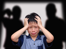 Crying asian boy. With his fighting parents in the background stock photos