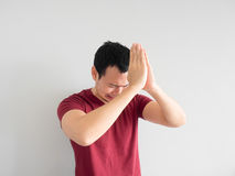 Sad man begging for forgiveness. Crying Asian man asking for forgiveness or begging the god for good fortune stock images