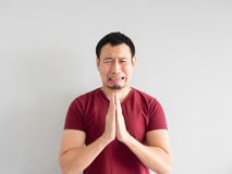 Sad man begging for forgiveness. Crying Asian man asking for forgiveness or begging the god for good fortune stock photo