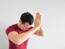 Sad man begging for forgiveness. Crying Asian man asking for forgiveness or begging the god for good fortune royalty free stock photography