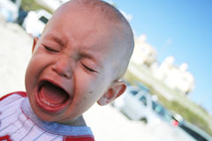 Crying baby. A baby at the beach with his family, crying because he cannot get his way! Arrgghh Stock Images