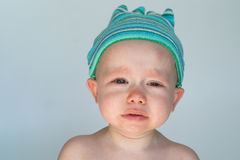 Crying Baby. Image of crying baby sitting in front of a white background Royalty Free Stock Image