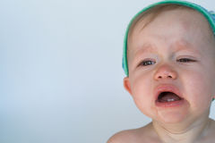 Crying Baby. Image of crying baby sitting in front of a white background Stock Photo