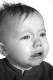 Crying Baby. Black and white image of crying baby sitting in front of a white background Royalty Free Stock Photos
