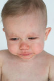 Crying Baby. Image of crying baby sitting in front of a white background Royalty Free Stock Photography