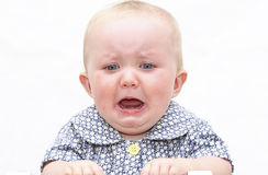 Crying baby. Upset crying baby teething against white background royalty free stock photo