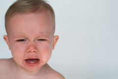 Crying Baby. Image of a cute crying baby sitting in front of a white background Royalty Free Stock Images