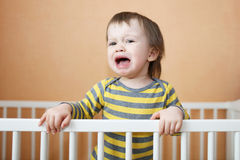 Crying baby in bed. Crying 18 months baby in white bed Stock Photo